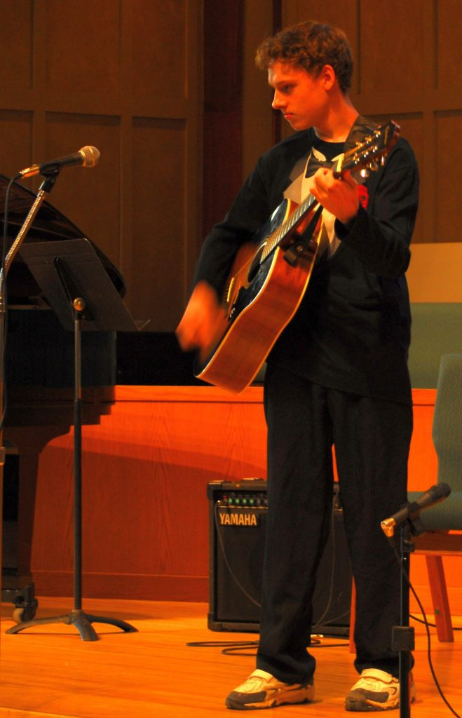 Boy singing and playing guitar