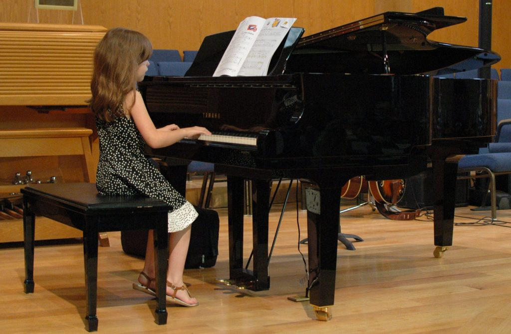 Tiny little girl playing paino