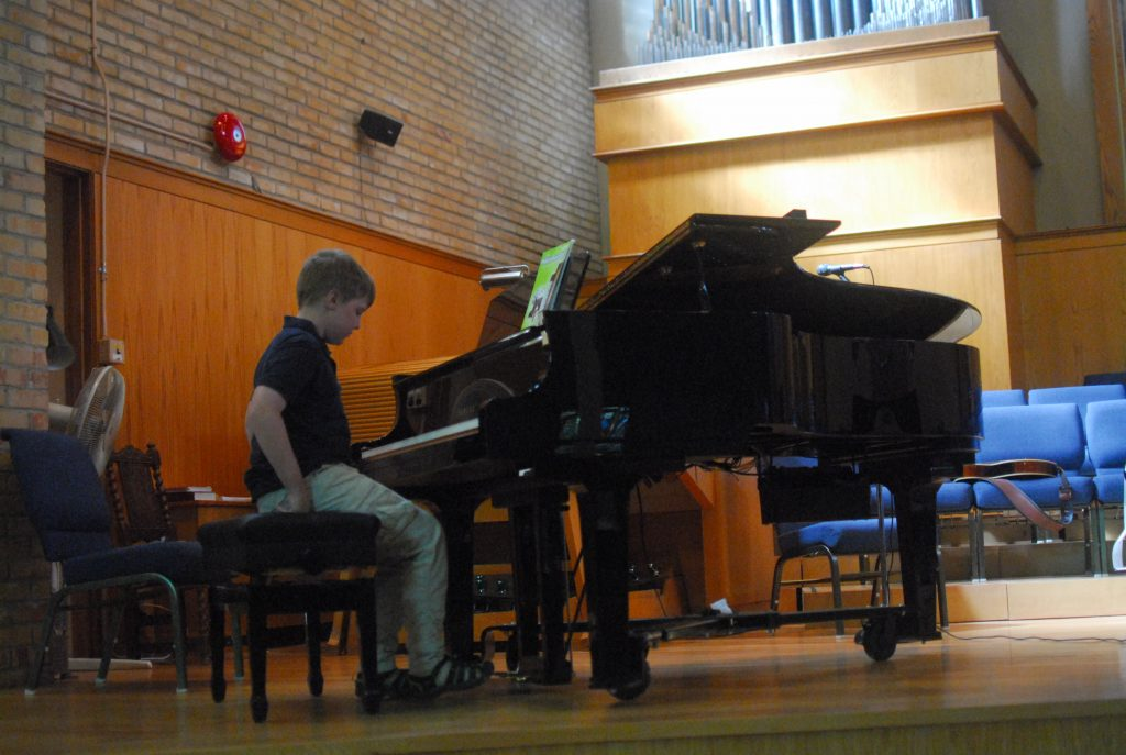 Boy getting ready to play piano