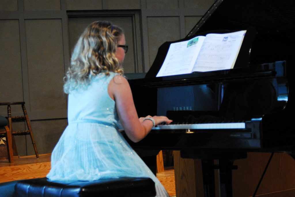 Girl with glasses playing piano