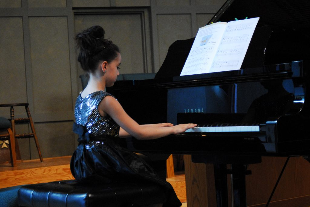 girl with up do playing piano
