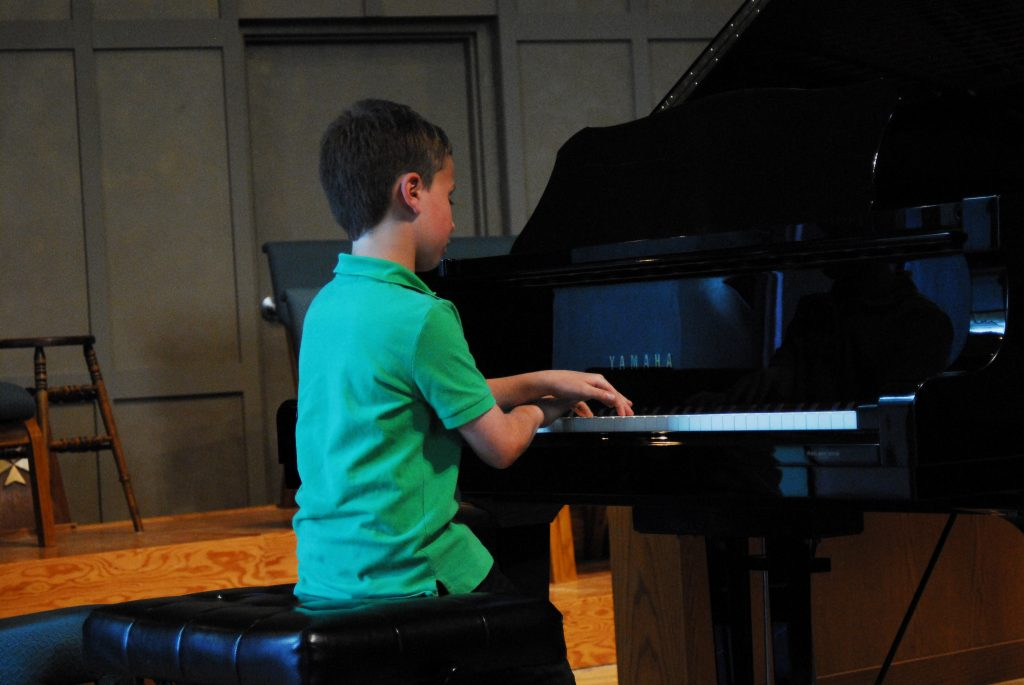 Boy doing cross hand technique on piano