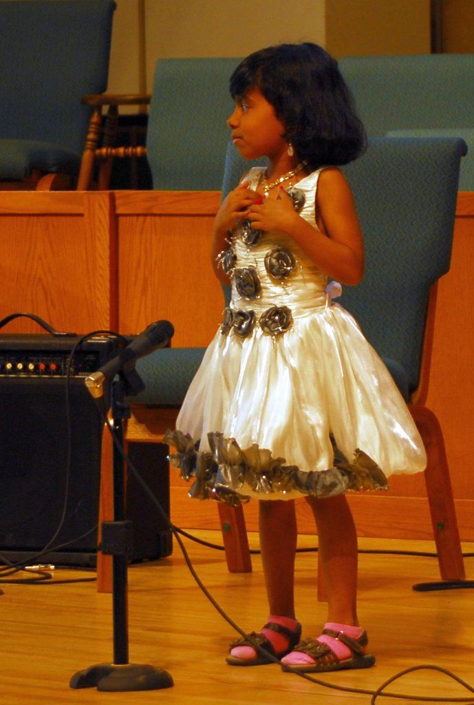 Little girl in rad dress singing